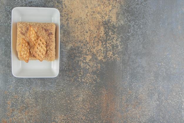 Tranche de gâteau avec des craquelins dans un plateau