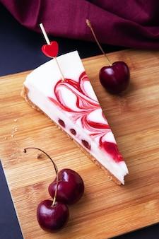 Une tranche de gâteau à la crème à l'air fait maison avec de la crème blanche et une garniture aux cerises. gâteaux blancs faits maison avec des baies fraîches d'été cerise sur une planche en bois. recette de dessert aux baies maison.