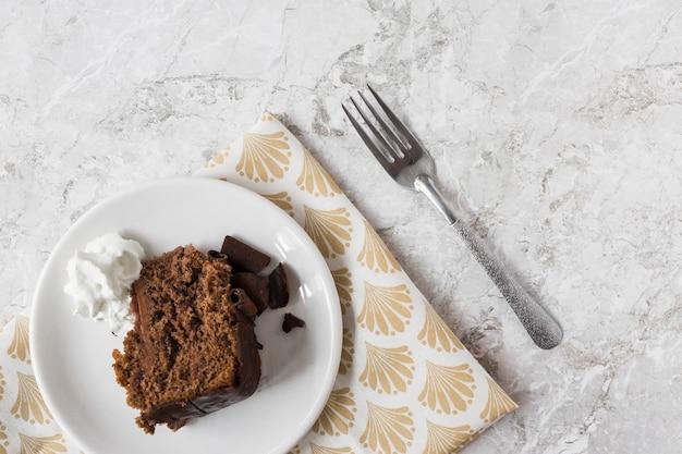 Tranche de gâteau avec de la crème fouettée sur une plaque sur le papier cadeau avec une fourchette