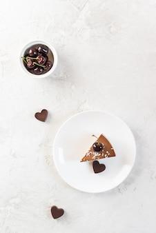Tranche de gâteau cru végétalien avec chocolat et cerise sur une plaque blanche