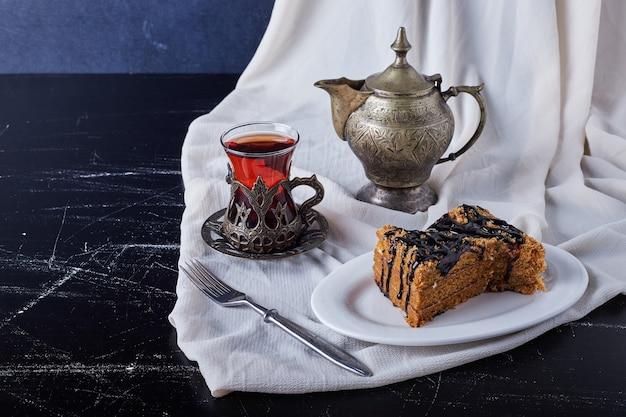 Tranche de gâteau dans une assiette blanche avec du sirop de chocolat et du thé.