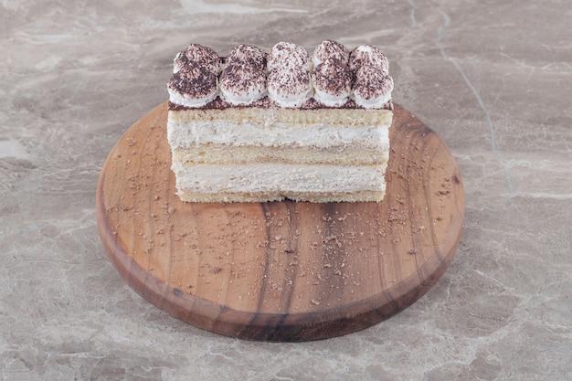 Tranche de gâteau garnie de crème et de cacao en poudre sur une planche sur marbre
