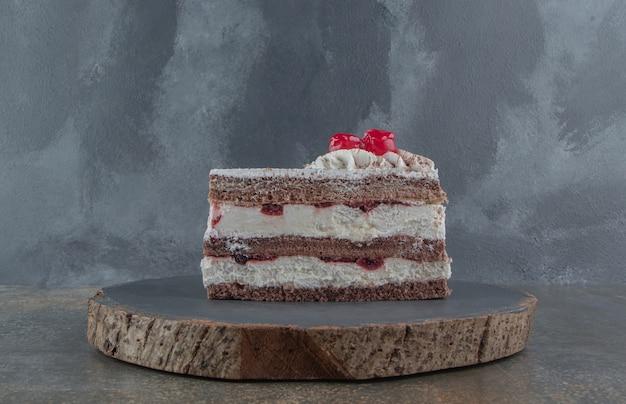 Tranche de gâteau garnie de crème et de cerise sur une planche