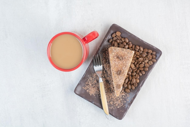 Tranche de gâteau avec grains de café et tasse de café. photo de haute qualité