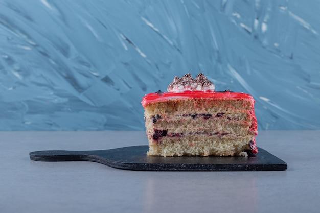 Tranche de gâteau maison fraîche sur une planche à découper en bois
