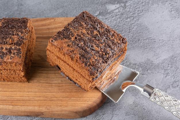 Tranche de gâteau maison fraîchement cuit sur planche de bois.