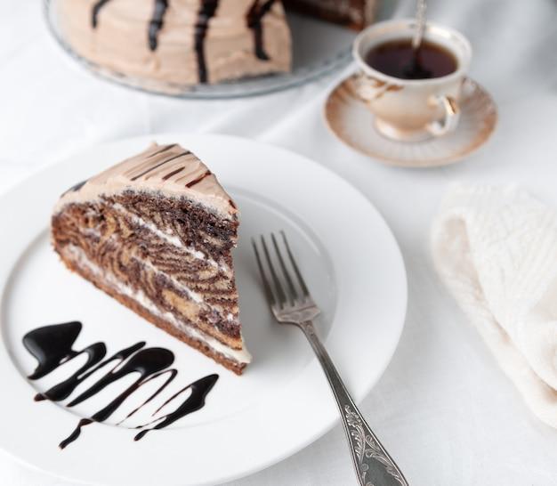 Une tranche de gâteau marbré à la crème garni de glaçage et de chocolat sur une plaque blanche avec une fourchette gros plan