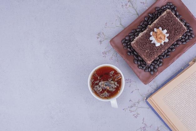 Une tranche de gâteau medovic avec du chocolat haché dans un plateau avec une tasse de tisane