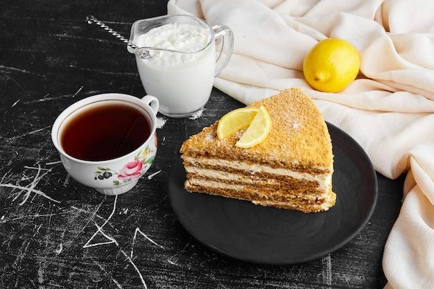 Une tranche de gâteau medovic avec du citron, du caillé et une tasse de thé.
