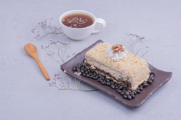 Une tranche de gâteau medovic avec des haricots au chocolat dans un plateau noir avec une tasse de thé