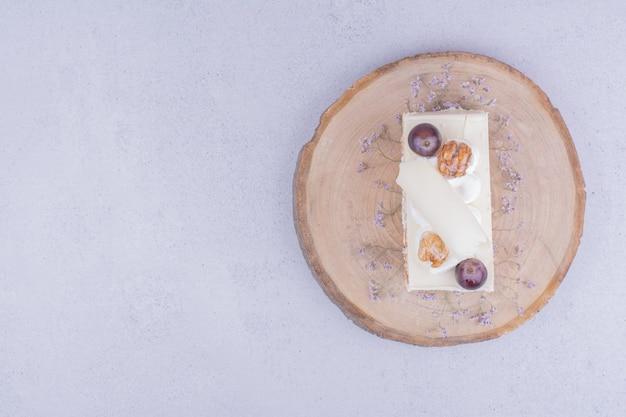 Une tranche de gâteau à la noix de coco avec raisins et noix sur une planche de bois