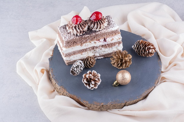 Tranche de gâteau avec des ornements de noël sur un morceau de bois.