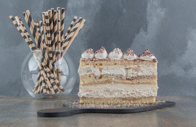 Tranche de gâteau sur une planche et un paquet de tuyaux de paille