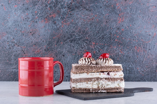 Tranche de gâteau sur une planche sombre avec une tasse de thé sur une table en marbre. photo de haute qualité