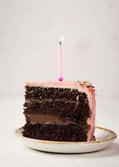 Tranche de gâteau savoureux avec bougie sur le dessus
