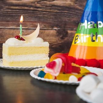 Tranche de gâteau; des sucreries; guimauve et chapeau d'anniversaire sur table