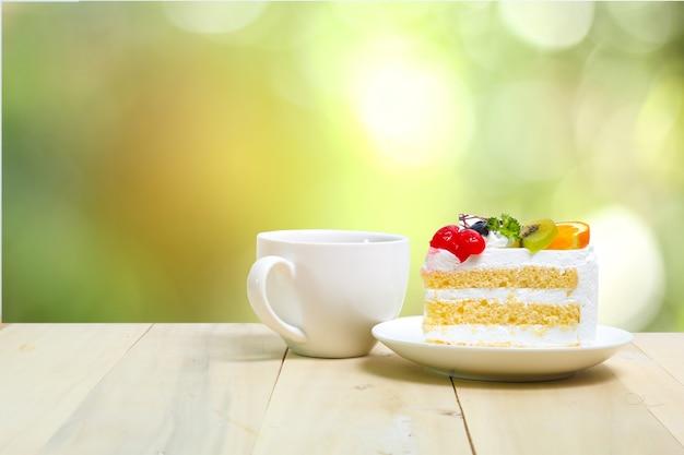 Tranche de gâteau avec une tasse de café sur bois, arrière-plan flou vert