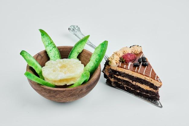 Une tranche de gâteau avec une tasse de fruits.