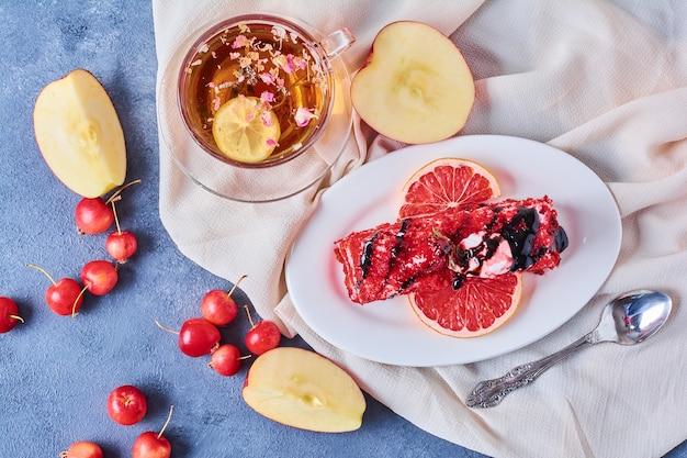Une tranche de gâteau de velours rouge dans une assiette blanche avec tisane