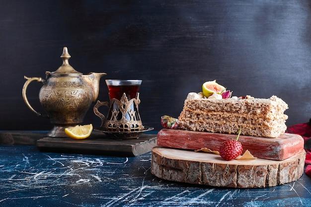 Une tranche de gâteau avec un verre de thé sur une surface bleue.
