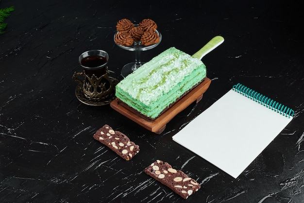 Une tranche de gâteau vert avec un livre de recettes.