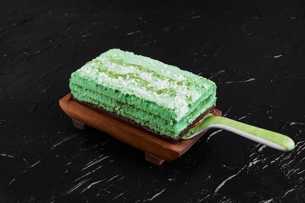 Une tranche de gâteau vert sur une planche de bois.