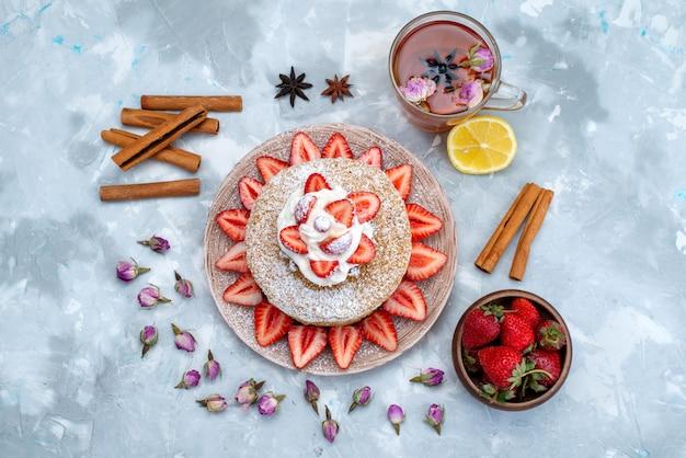 Une tranche de gâteau vue de dessus avec de la crème fraises rouges fraîches à l'intérieur de la plaque avec de la cannelle et du thé sur le fond bleu-gris