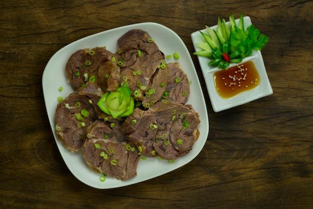 Tranche de jarrets de bœuf braisée servie sauce à l'huile de sésame décorer le concombre et les légumes sculptés taiwan plat d'apéritif populaire dans