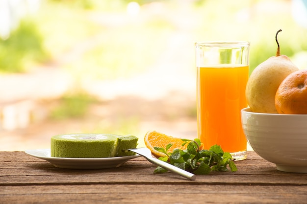 Tranche et jus d'orange et d'orange à la menthe et gâteau au thé vert sur une table en bois.
