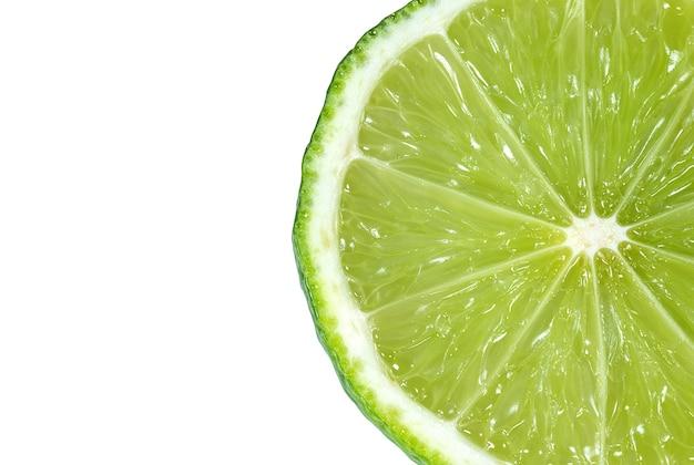 Tranche juteuse d'agrumes citron vert gros plan sur blanc