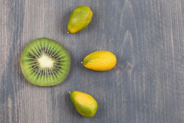 Tranche de kiwi avec de petites mandarines sur une surface en marbre