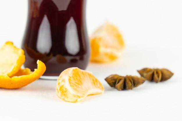 Une tranche de mandarine devant un verre de vin rouge chaud pour un apéritif du nouvel an