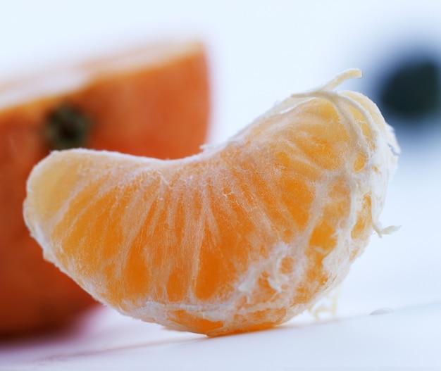 Tranche d'une mandarine mûre sur blanc