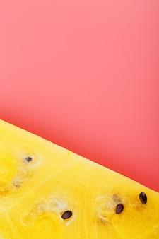 Tranche de melon d'eau jaune sur une rose. été lumineux