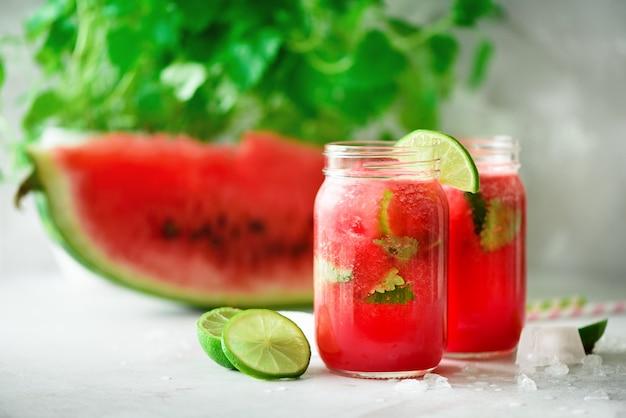 Tranche de melon d'eau rouge fraîche et smoothie dans un bocal en verre avec paille, glace, menthe, citron vert sur fond clair