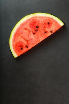 Tranche de melon d'eau rouge juteuse sur pierre noire