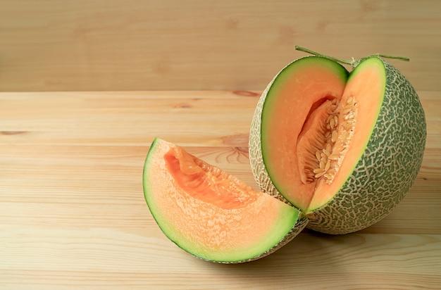 Tranche de melon mûr frais tranché du fruit entier sur une table en bois