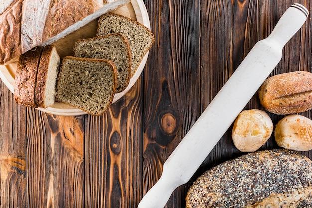 Tranche et miches de pain avec rouleau à pâtisserie sur un bureau en bois
