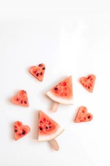 Tranche mûre de pastèque sous forme de coeur sur un bâton sur une nourriture saine de fond blanc