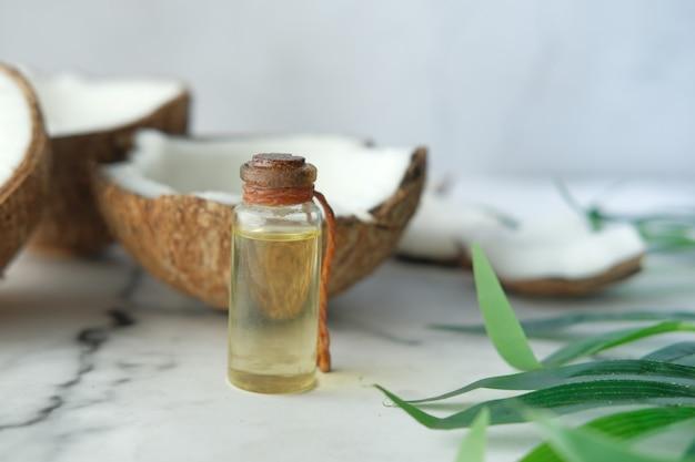 Tranche de noix de coco fraîche et bouteille d'huile sur une table