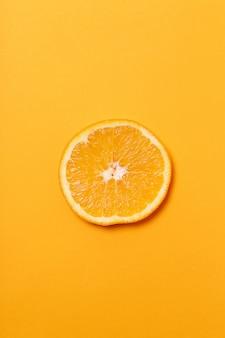 Tranche d'orange isolée sur une surface orange