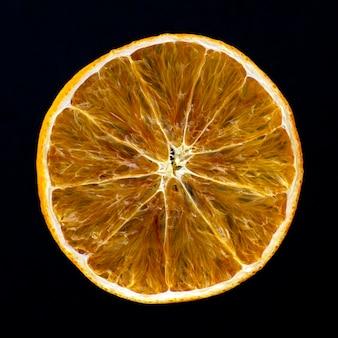 Tranche d'orange séchée sur un fond sombre