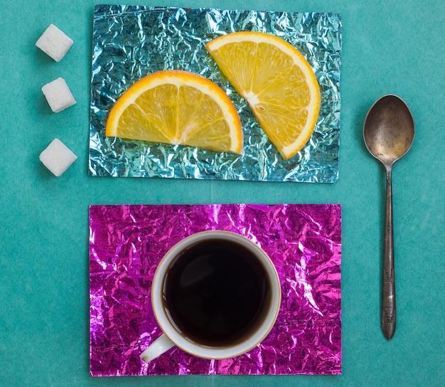 Tranche d'orange et une tasse de café sur des supports en papier d'aluminium jaune et turquoise sur une surface en bois
