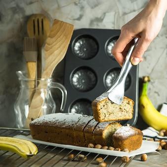 Une tranche de pain à la banane dans la pince dans la main féminine