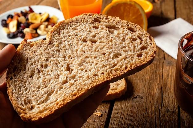 Tranche de pain complet biologique sur table rustique