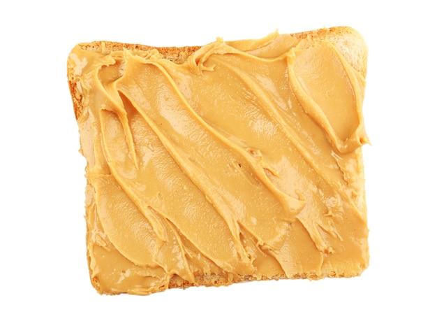 Tranche de pain avec du beurre d'arachide crémeux isolé sur blanc