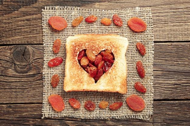 Tranche de pain en forme de coeur découpé et fruits secs sur table en bois