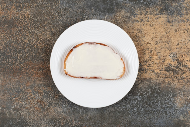Tranche de pain grillé avec de la crème sure sur une assiette blanche.
