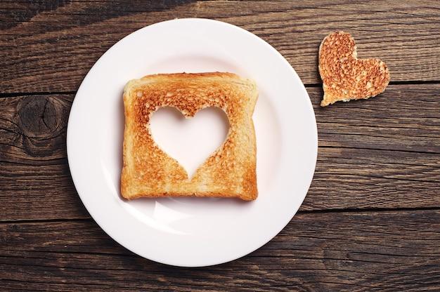 Tranche de pain grillé avec forme de coeur découpé sur fond de bois