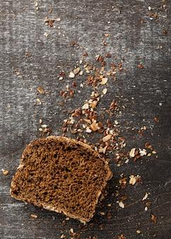 Tranche de pain avec miettes et grains vue de dessus